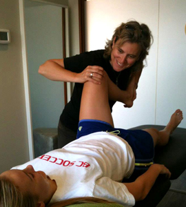 Assessing hip and knee mobility in a soccer player.